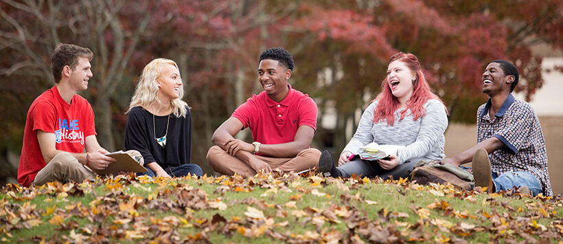 Five UWG students seated outside in autumn