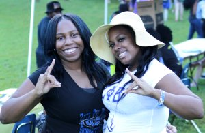 Two members of Zeta Phi Beta Sorority, Incoporated throwing their hand signs at Welcome Back Blast