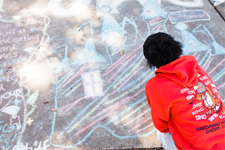 A student drawing the sidewalk as a part of the Homecoming Sidewalk Chalking Contest