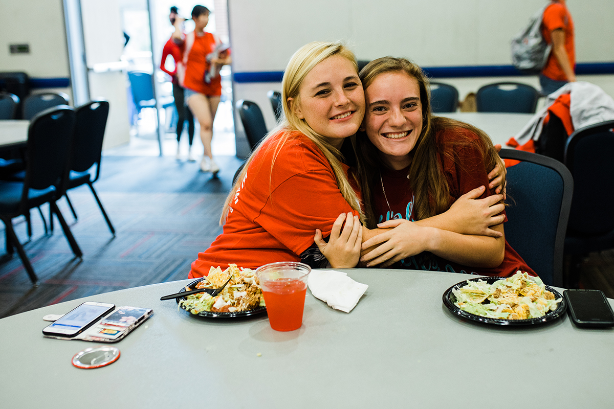 Two students embracing while they enjoy the Wear Red Get Fed event hosted by the Student Activities Council