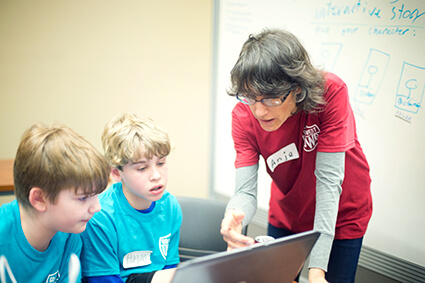 Dr. Anja Robinson assists two middle-school aged students in their work at a computer.
