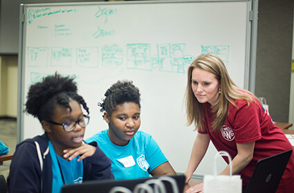 Lindsey Robinson leans near two teenage students to look at their work on a computer.