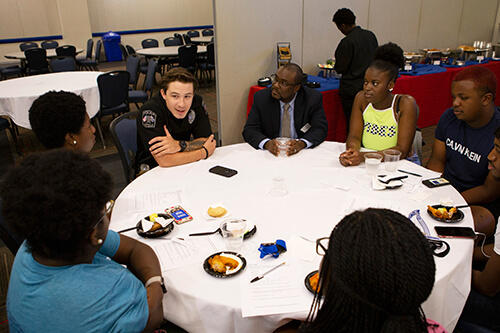 Police and UWG personnel chat with students at a table
