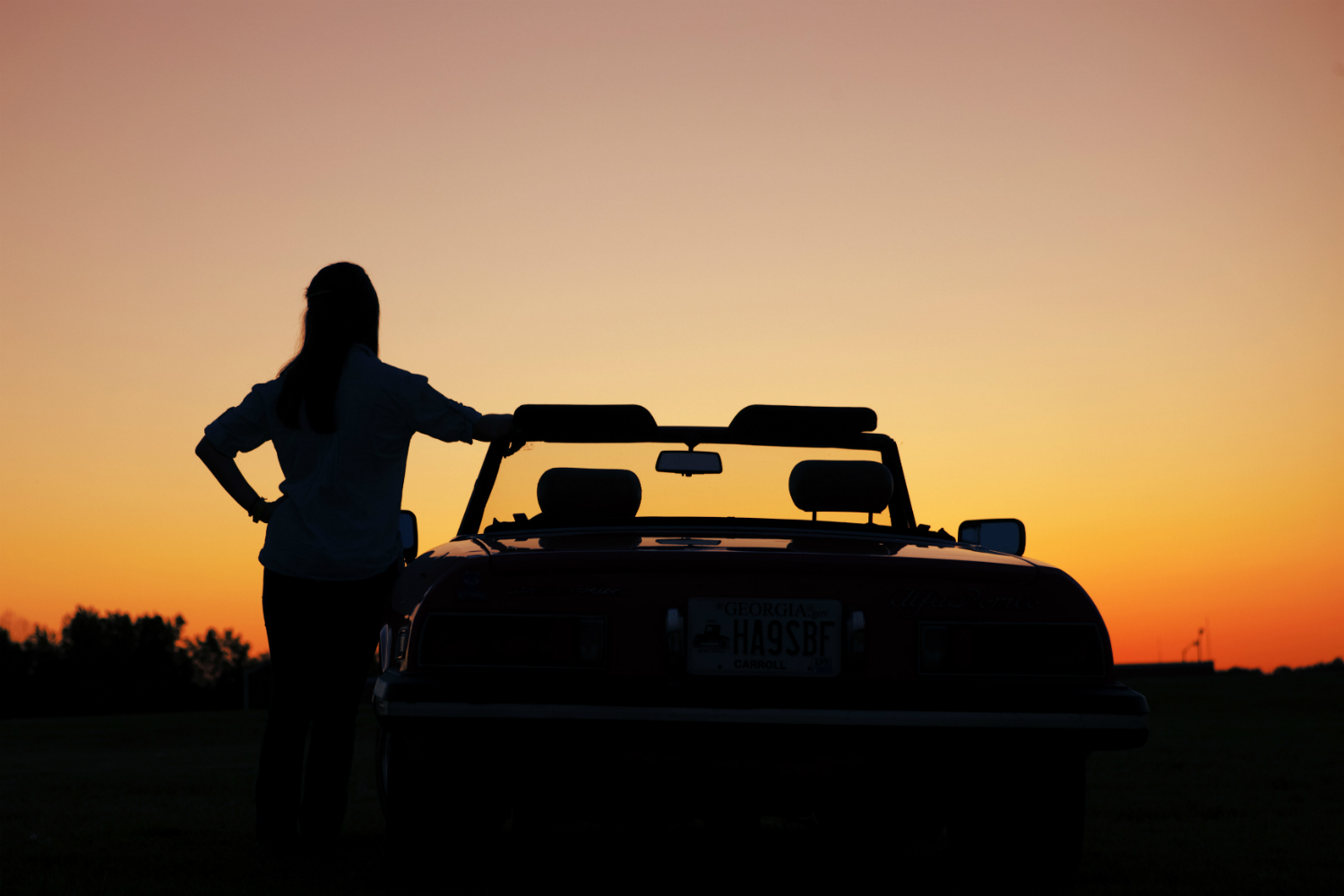 girl standing at her vehicle looking at the sunset